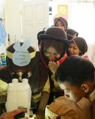 Children looking at insects in a microscope. [Foto: Klas Inspirasi Jambi]